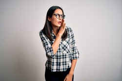 Young brunette woman with blue eyes wearing casual shirt and glasses over white background hand on mouth telling secret rumor, whispering malicious talk conversation