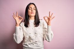 Young brunette woman with blue eyes wearing casual sweater over isolated pink background relax and smiling with eyes closed doing meditation gesture with fingers. Yoga concept.