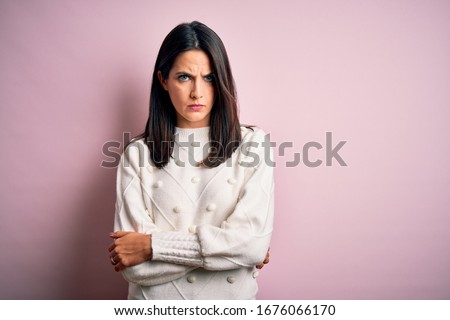 Young brunette woman with blue eyes wearing casual sweater over isolated pink background skeptic and nervous, disapproving expression on face with crossed arms. Negative person. Foto stock ©