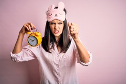 Young brunette woman with blue eyes wearing pajama and eye mask holding alarm clock annoyed and frustrated shouting with anger, crazy and yelling with raised hand, anger concept