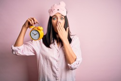 Young brunette woman with blue eyes wearing pajama and eye mask holding alarm clock cover mouth with hand shocked with shame for mistake, expression of fear, scared in silence, secret concept