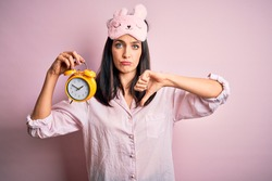 Young brunette woman with blue eyes wearing pajama and eye mask holding alarm clock with angry face, negative sign showing dislike with thumbs down, rejection concept