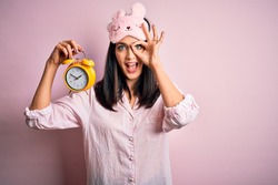 Young brunette woman with blue eyes wearing pajama and eye mask holding alarm clock with happy face smiling doing ok sign with hand on eye looking through fingers