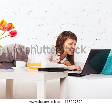 Young brunette woman with happy smile lying on the sofa with laptop