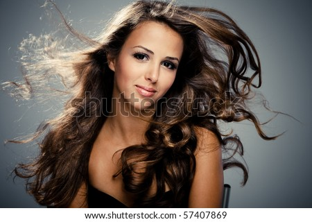 young brunette  woman with long flying hair, studio shot