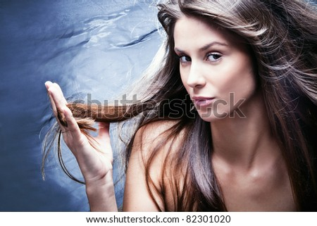 young brunette woman with nourished long  hair, studio shot, profile, small amount of grain added