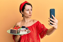 Young brunette woman with short hair holding sweets cakes taking a selfie picture depressed and worry for distress, crying angry and afraid. sad expression.
