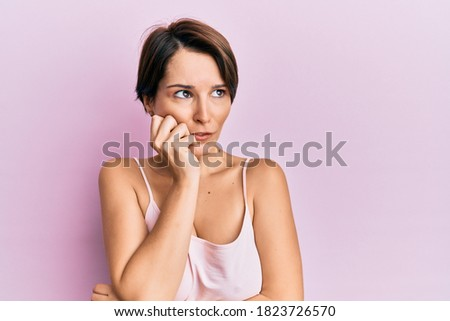 Young brunette woman with short hair over pink background looking stressed and nervous with hands on mouth biting nails. anxiety problem.  stock photo