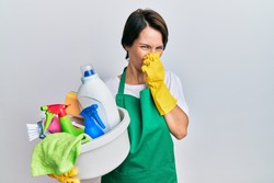 Young brunette woman with short hair wearing apron holding cleaning products smelling something stinky and disgusting, intolerable smell, holding breath with fingers on nose. bad smell