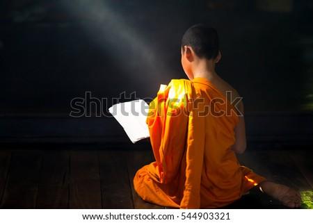 Young Buddhist novice monk reading, Young Buddhist novice monk study inside monastery, Ayutthaya, Thailand