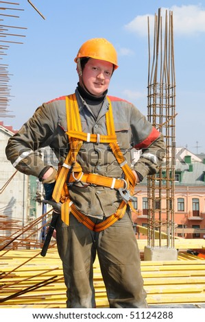 Young builder worker in work wear, helmet and equipment at house building area