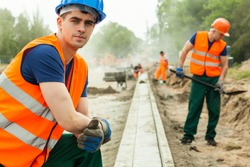 Young building worker on knees installing kerb on the road