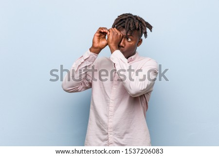 Young business african black man looking far away keeping him hand on forehead.