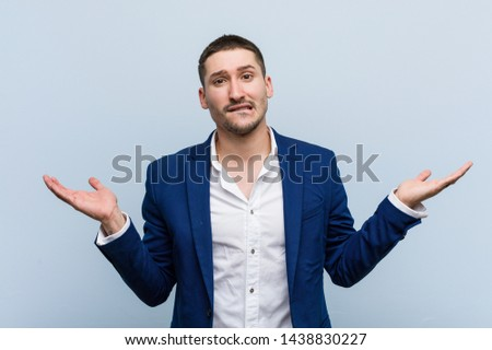 Young business caucasian man confused and doubtful raising him hands to hold a copy space.