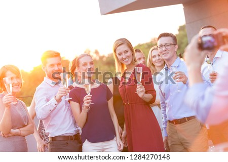 Young business colleagues talking while standing at rooftop during party