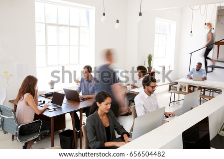 Young business colleagues working in a busy open plan office ストックフォト ©