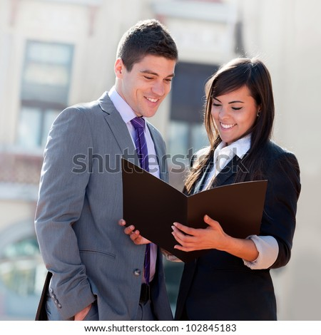 Young Business couple looking at file outdoors.