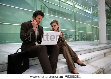 Young business couple sat on steps