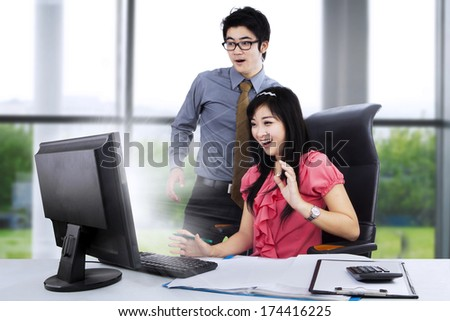 Young business couple shocked in front of computer on the desk