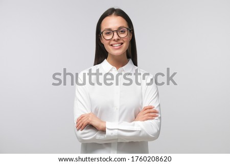 Young business girl in white collar shirt and eyeglasses laughing happily, standing with arms crossed, looking confident, isolated on gray background Foto stock ©