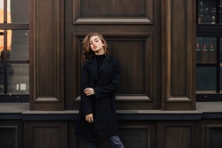 Young business lady standing near expensive restaurant. Fashion portrait of a caucasian young girl near her restaurant. Girl standing. Woman dressed in black coat and jeans.
