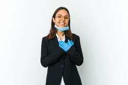Young business latin woman wearing a mask to protect from covid isolated on white background has friendly expression, pressing palm to chest. Love concept.