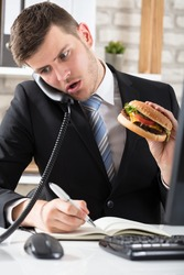 Young Business Man At Desk Eating Burger And Working At Workplace