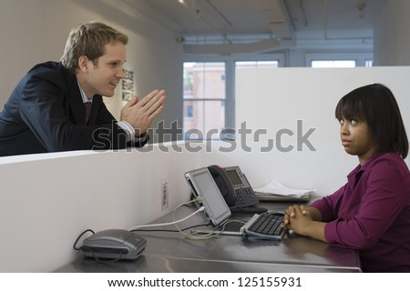 Young business man begging woman in office cubicle