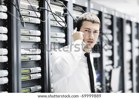 young business man computer science engineer talking by cellphone at network data center server room asking  for help and fast solutions and services