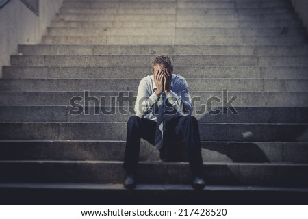 Young business man crying abandoned lost in depression sitting on ground street concrete stairs suffering emotional pain, sadness, looking sick in grunge lighting Stock photo ©