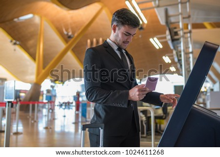 Young business man doing self check in a machine at the airport  #1024611268