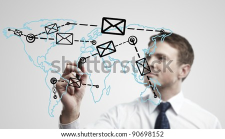 Young business man drawing a global network with envelopes on world map. Man drawing  E-mail Icon on a glass window. The metaphor of international communication around the world. On a gray background.