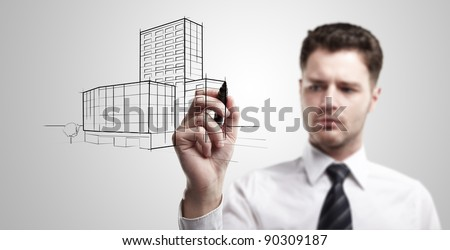 Young business man drawing a project of building on a glass window. Portrait of young architect thinking about construction. On a gray background.