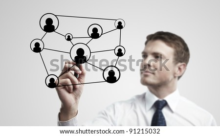 Young business man drawing a social network or globalization concept. Man drawing a global network on a glass window. On a gray background.