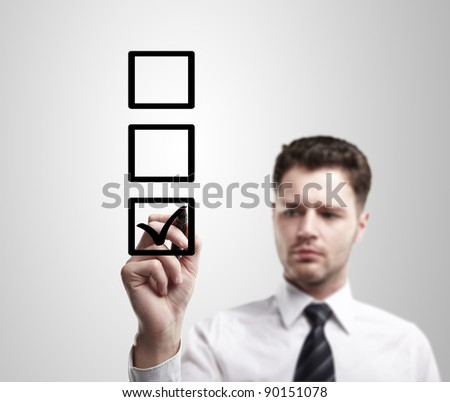Young business man drawing a tick on a glass window in an office. Man choosing one of three options. On a gray background