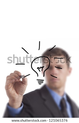 Young business man draws a lightbulb.
