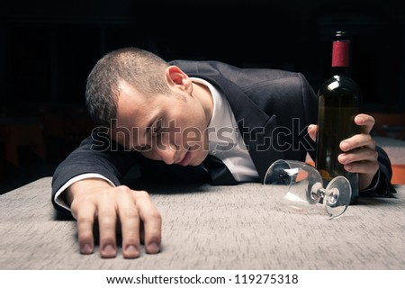 Young business man drunk felt asleep with red wine.