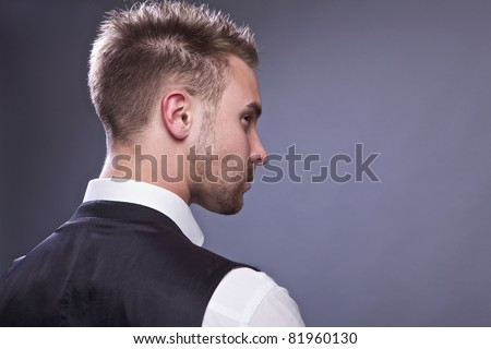 Young business man from back, isolated on gray.