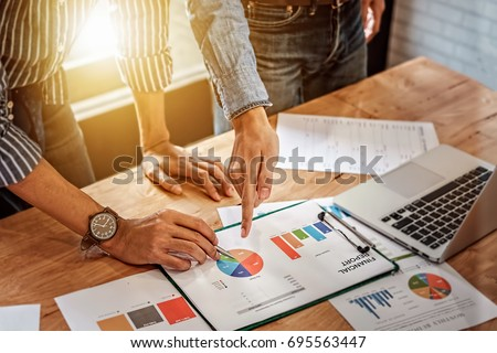 young business man hand holding pen and partner pointing graph chart for  analyze the company's sales plan in the office. #695563447