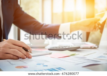 Young business man hand holding pen  with using laptop computer, calculator and post it node on wood desk for  Plans to improve quality next month in office.