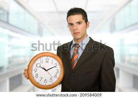 young business man holding a clock at the office