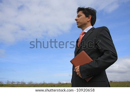 Young business man holding a executive notebook ready to work on the nature