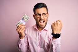 Young business man holding bunch of 20 dollars banknotes over pink isolated background annoyed and frustrated shouting with anger, crazy and yelling with raised hand, anger concept