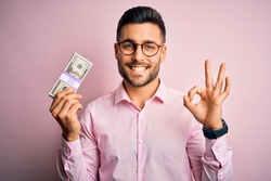 Young business man holding bunch of 20 dollars banknotes over pink isolated background doing ok sign with fingers, excellent symbol
