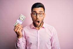 Young business man holding bunch of 20 dollars banknotes over pink isolated background scared in shock with a surprise face, afraid and excited with fear expression