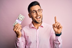 Young business man holding bunch of 20 dollars banknotes over pink isolated background surprised with an idea or question pointing finger with happy face, number one