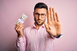 Young business man holding bunch of 20 dollars banknotes over pink isolated background with open hand doing stop sign with serious and confident expression, defense gesture