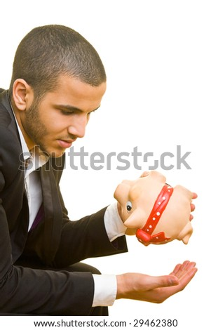 Young business man holding his hand under an empty piggy bank