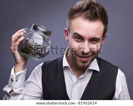 Young business man holding jar with coins  - retirement fund and savings concept