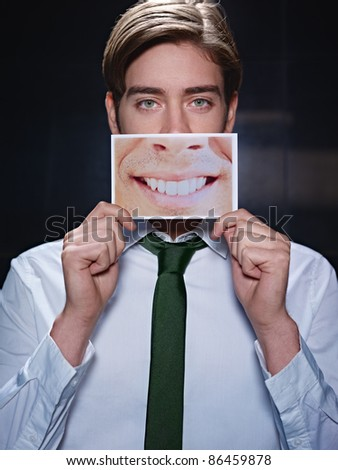 young business man holding photo of toothy smile on black background. Vertical shape, front view, waist up
